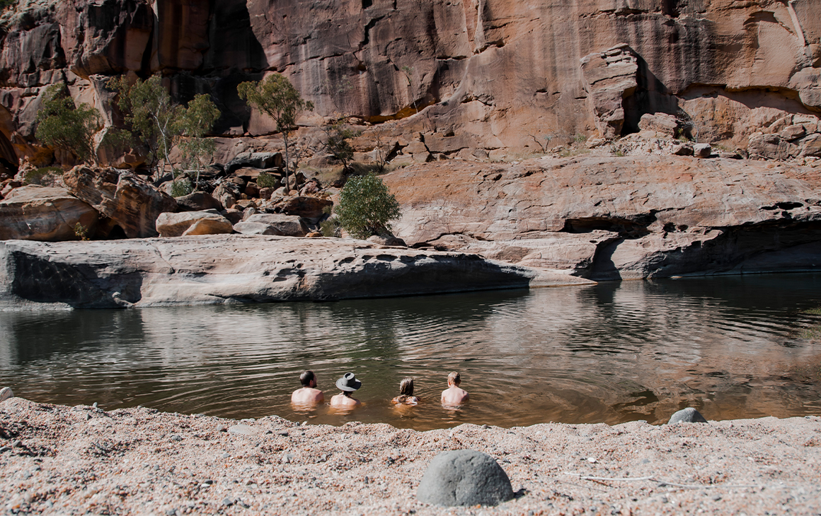 four people sitting in a watering hole under a cliff