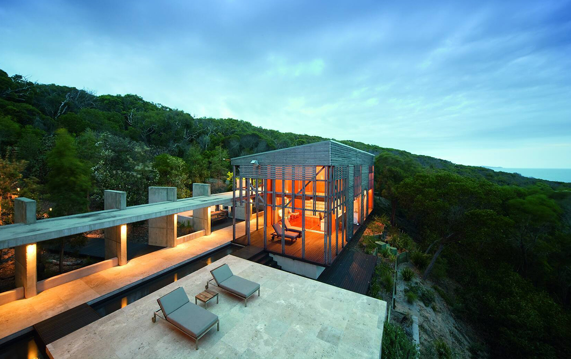 A designer concrete hideaway perched on the edge of a cliff.