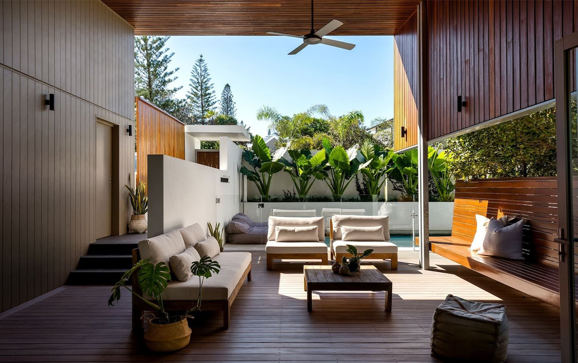 Massive outdoor space with high ceilings and lounging furniture in front of a pool.