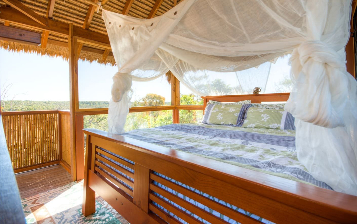 A canopied bed in a tree-house style cabin.