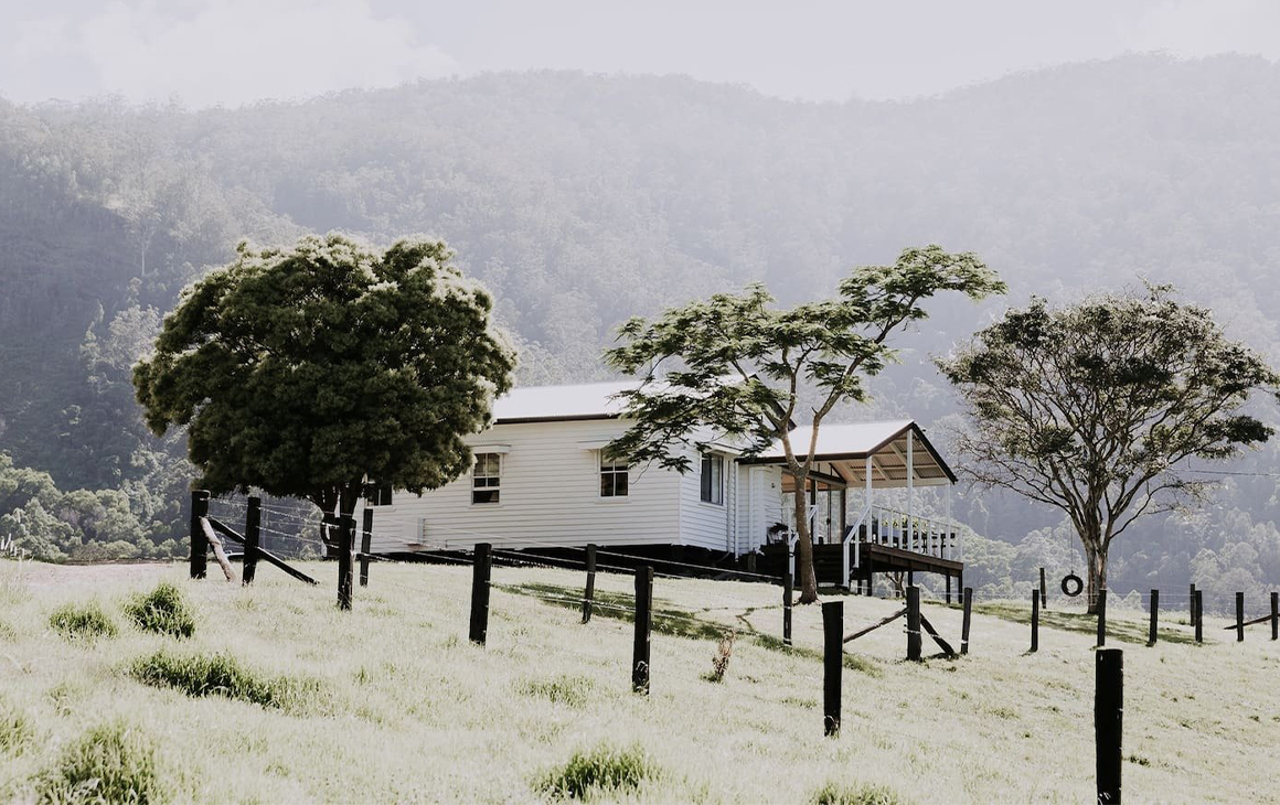 A white cottage in the middle of a farm paddock.