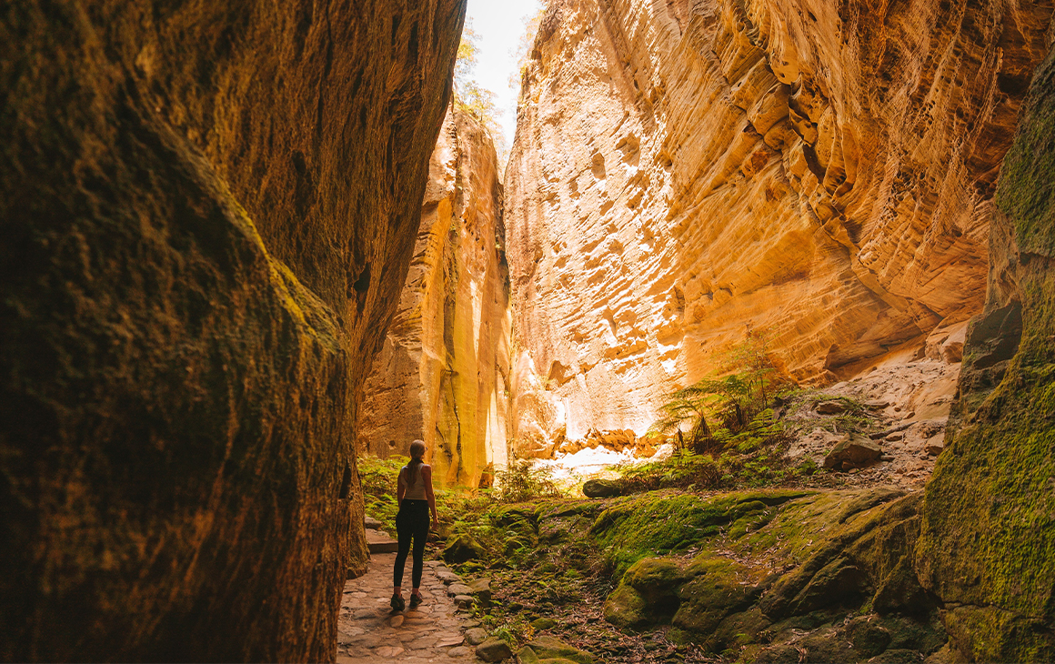 a person standing in a deep, narrow gorge