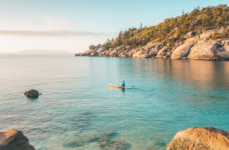 a person kayaking through aqua ocean waters in front of a granite boulder covered hill