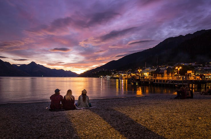 Three people watching the sunset on Queenstown Bay.