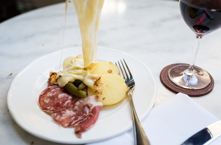 melted cheese being tipped on to a plate of potato, salami and pickles