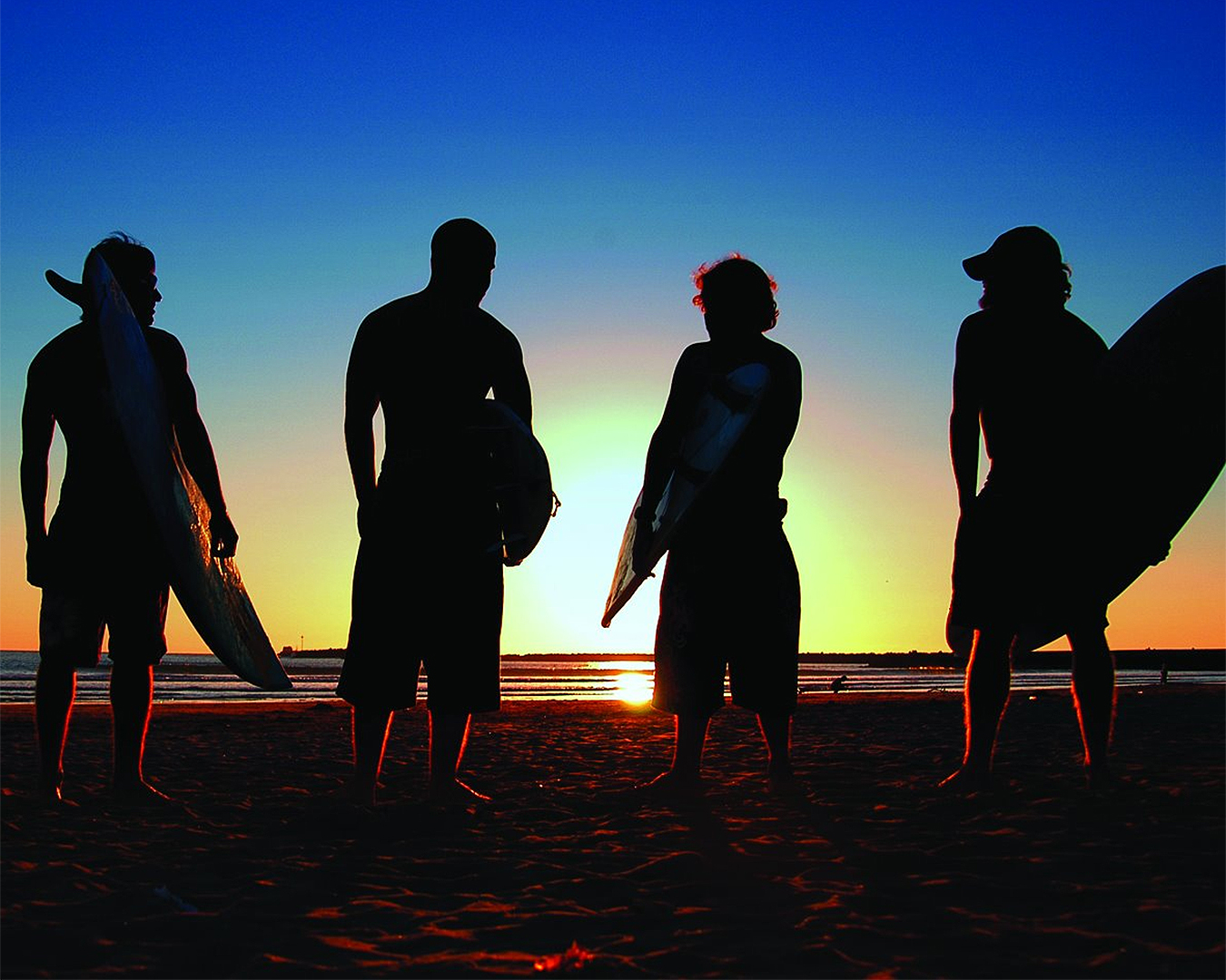 Surfers at sunset near Raglan Holiday Park.