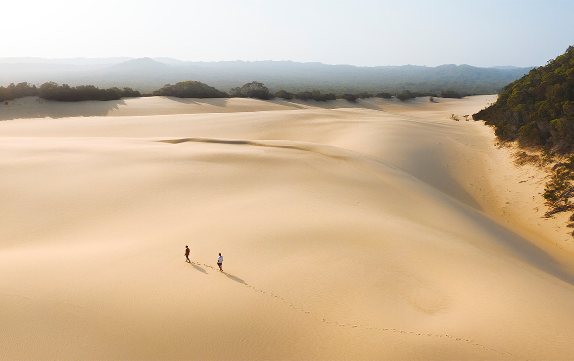 Two tiny people (far away) walking on a massive patch of sand, seen from above