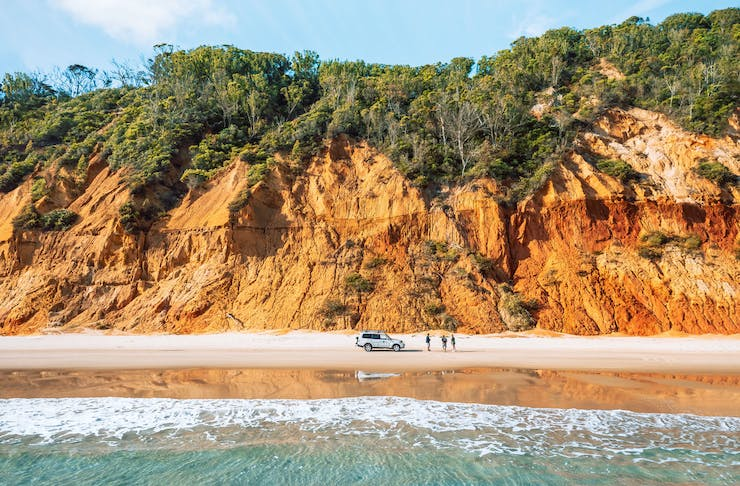 The Coloured Sands is an orange-coloured cliff face that runs along the beach near Rainbow Beach.