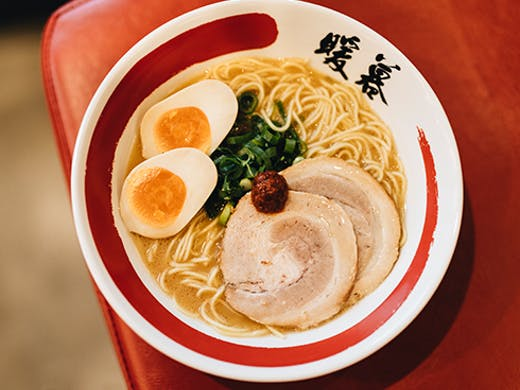 A bowl of ramen topped with pork and eggs