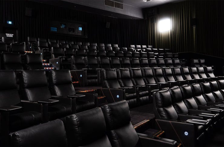 a dark cinema lined with reclining chairs