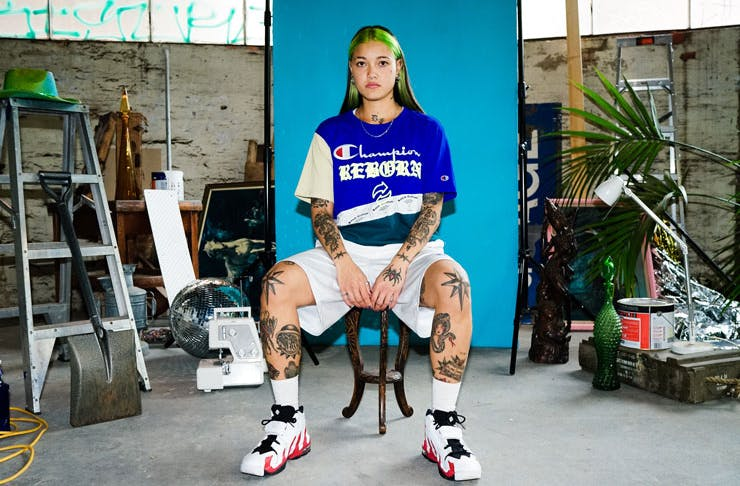A girl sitting on a chair wearing the new REBORN x Champion up-cycled collection.