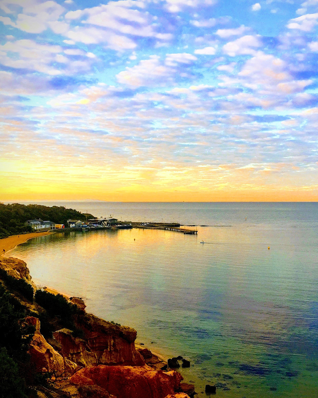 Red Bluff bay at sunset, with a dreamy sky, red cliff coastline and blue water.