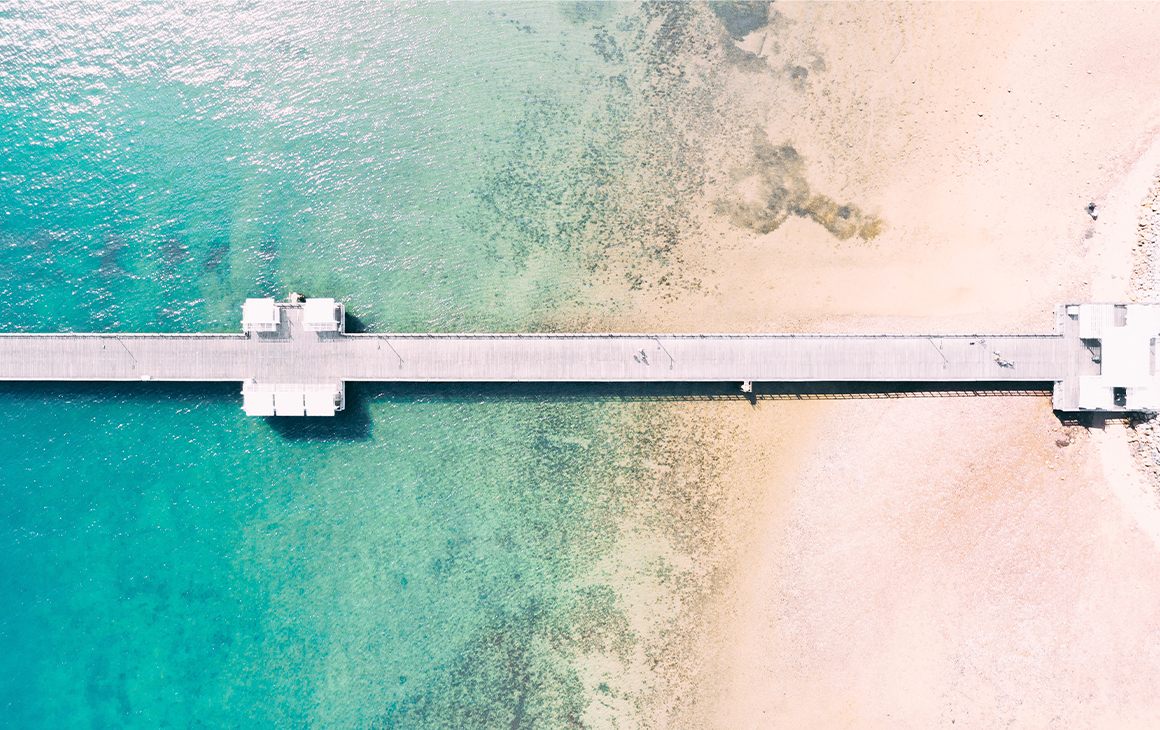 A long jetty stretching out over white sand and aqua water