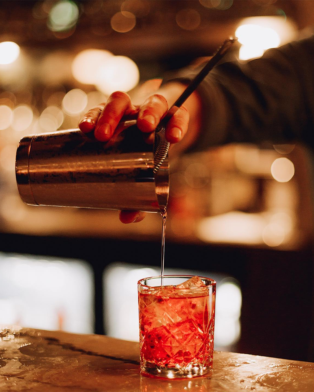 A drink is poured at Reign & Pour.