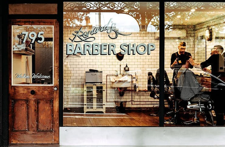 An old school barbershop with a sign on the window that reads