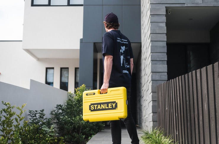 A Rendr deliveryman stands outside a house with a Stanley box.