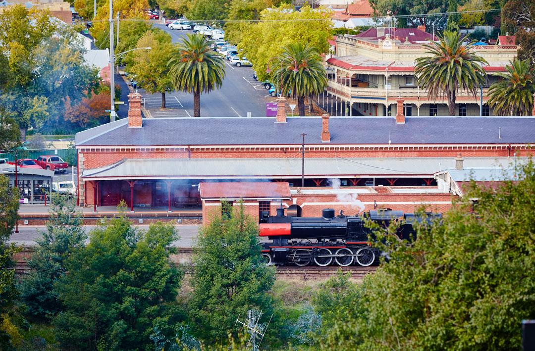A steam train departs Castlemaine railway station.