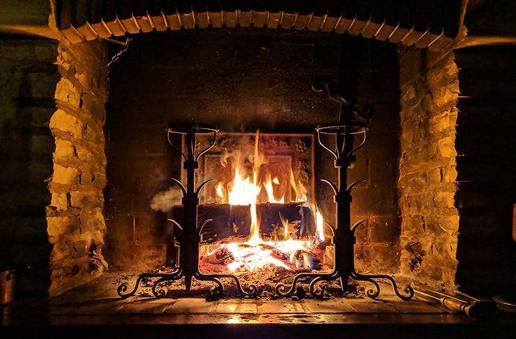 A cosy looking hearth with a roaring fire.