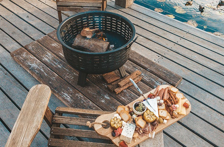a fire pit with a cheeseboard