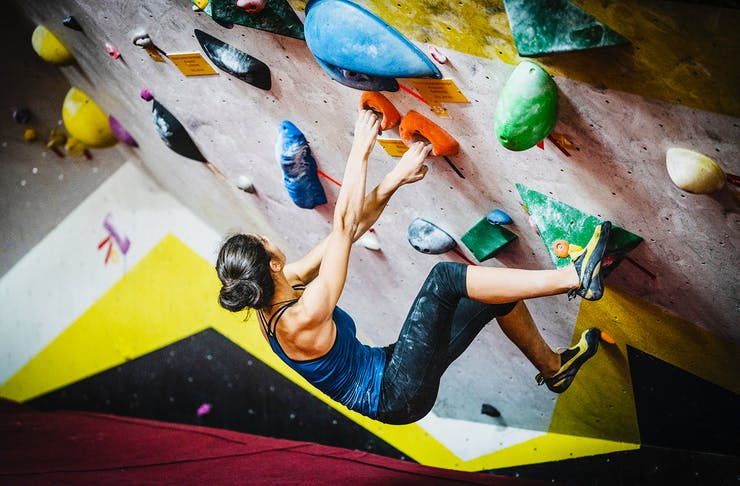 A girl scales a rock climbing wall with aplomb.