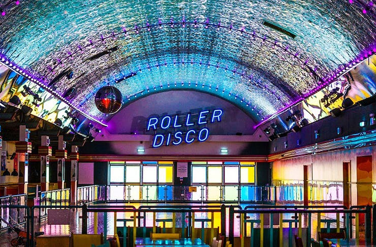 A view of a roller disco with bright neon lights.