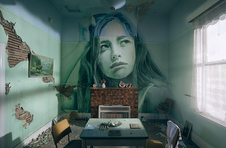 A detailed painting of a woman on a wall inside a dilapidated cottage.