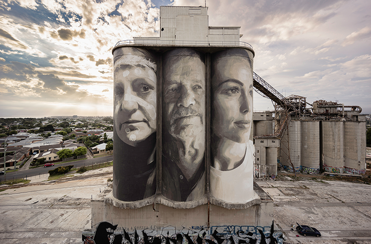 Three portraits painted on the front of three large silos.