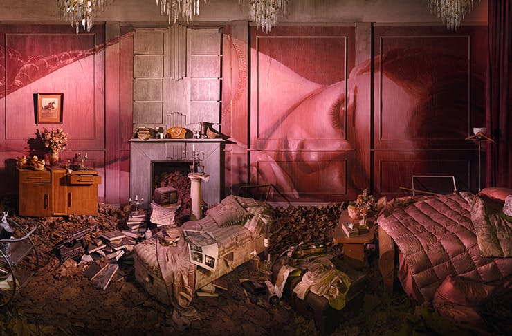 A pink room covered in work from artist Rone.