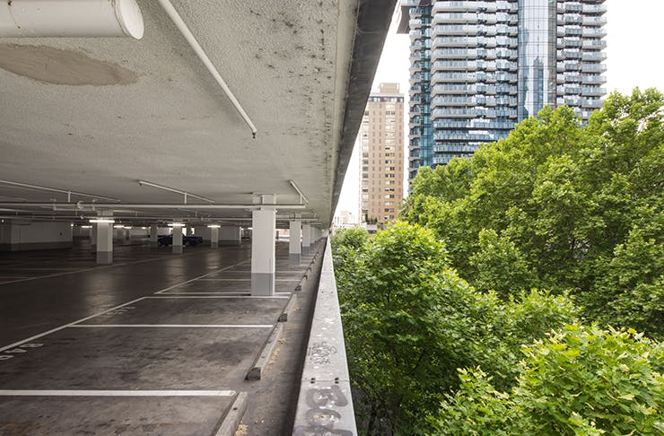 A rooftop carpark in Melbourne CBD. Several trees and the citt skyline can be seen in the background.
