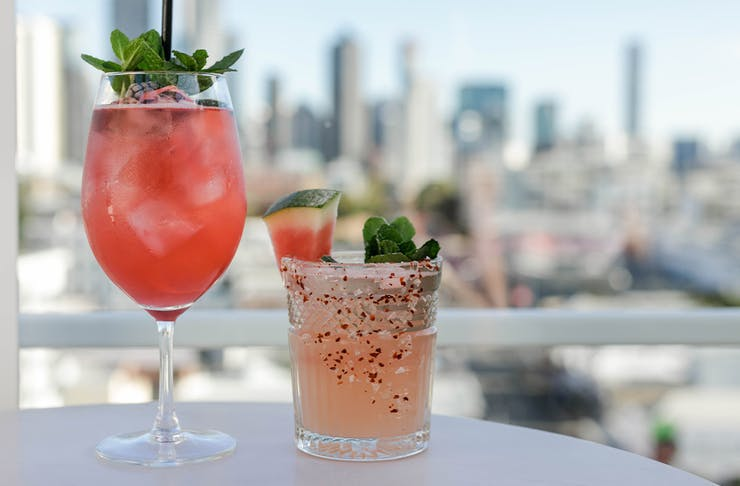 two cocktails in front of a view of a city skyline