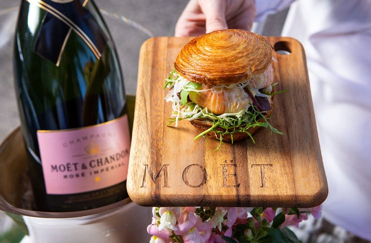 a croissant roll filled with bug next to a bottle of champagne