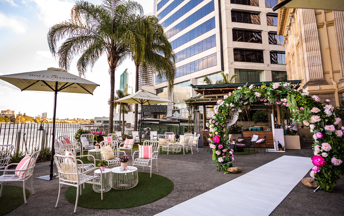 a riverside bar area with a floral arch