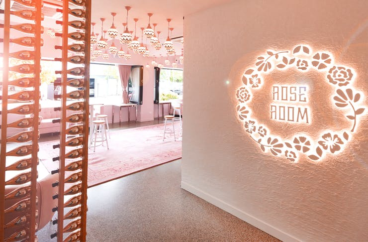 entry to rose room, with the name in lights on a wall