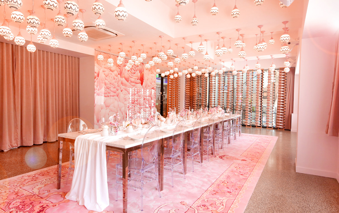 a pink room with a long dining table set in the middle