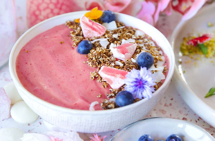 a pink smoothie bowl topped with granola