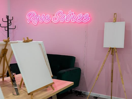 a neon sign in a paint and sip studio
