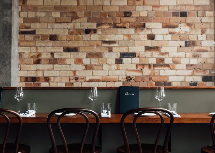 bar seating in front of a brick wall