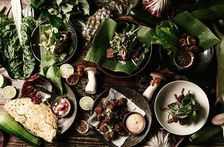 Several earthy vegan dishes spread out on a table.