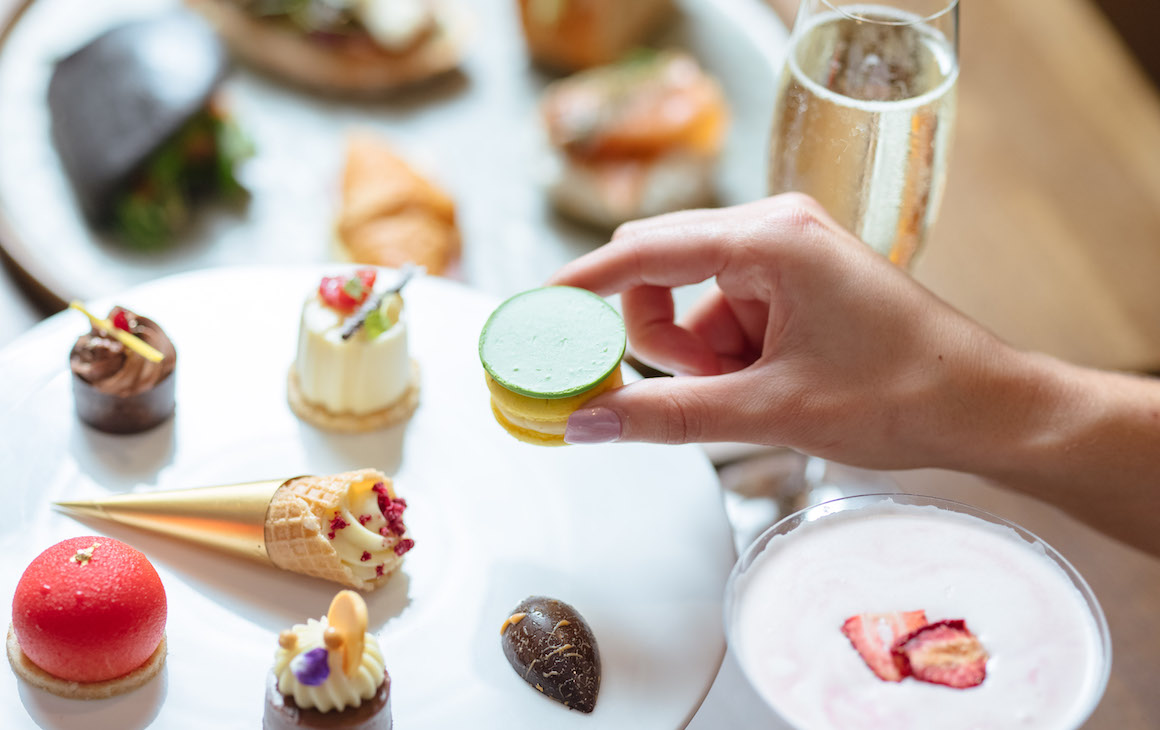 a diner reaches for a delicate sweet treat from the Mother's Day high tea at Samuels On Mill
