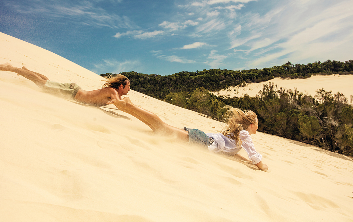two people boarding down a sand dune