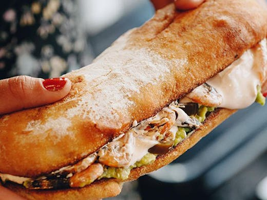 An extra large sandwich dripping with mayonnaise.