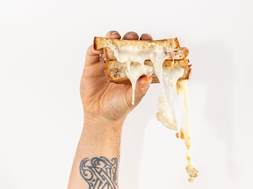A cheese sandwich being held in one hand. The man's arm is covered in tattoos.