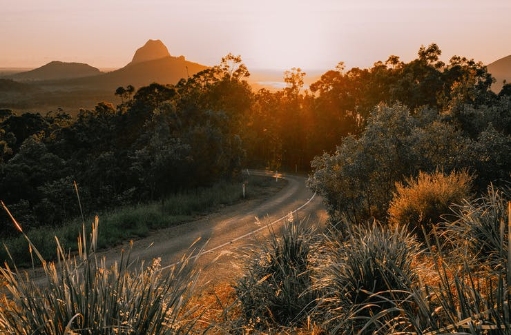 An empty, winding road on the Sunshine Coast, with the Glass House Mountains in the background.