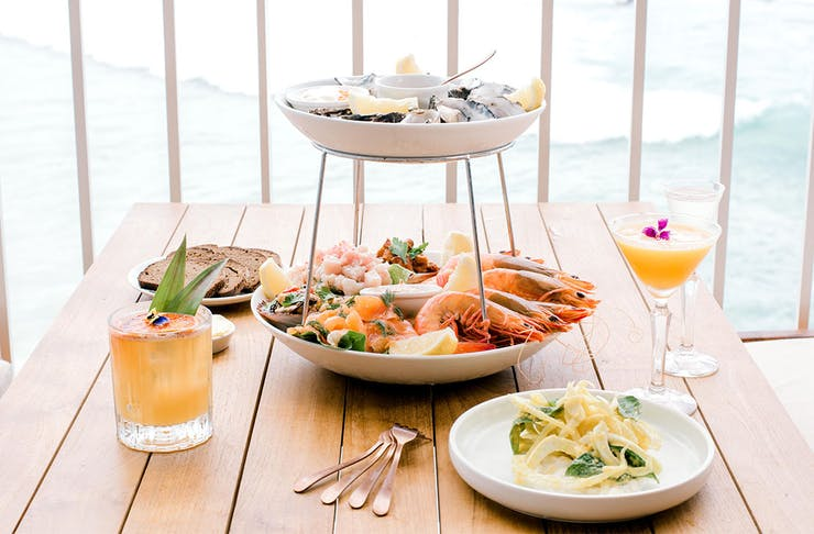 A tiered seafood platter on a table, overlooking the beach at Burleigh Heads.