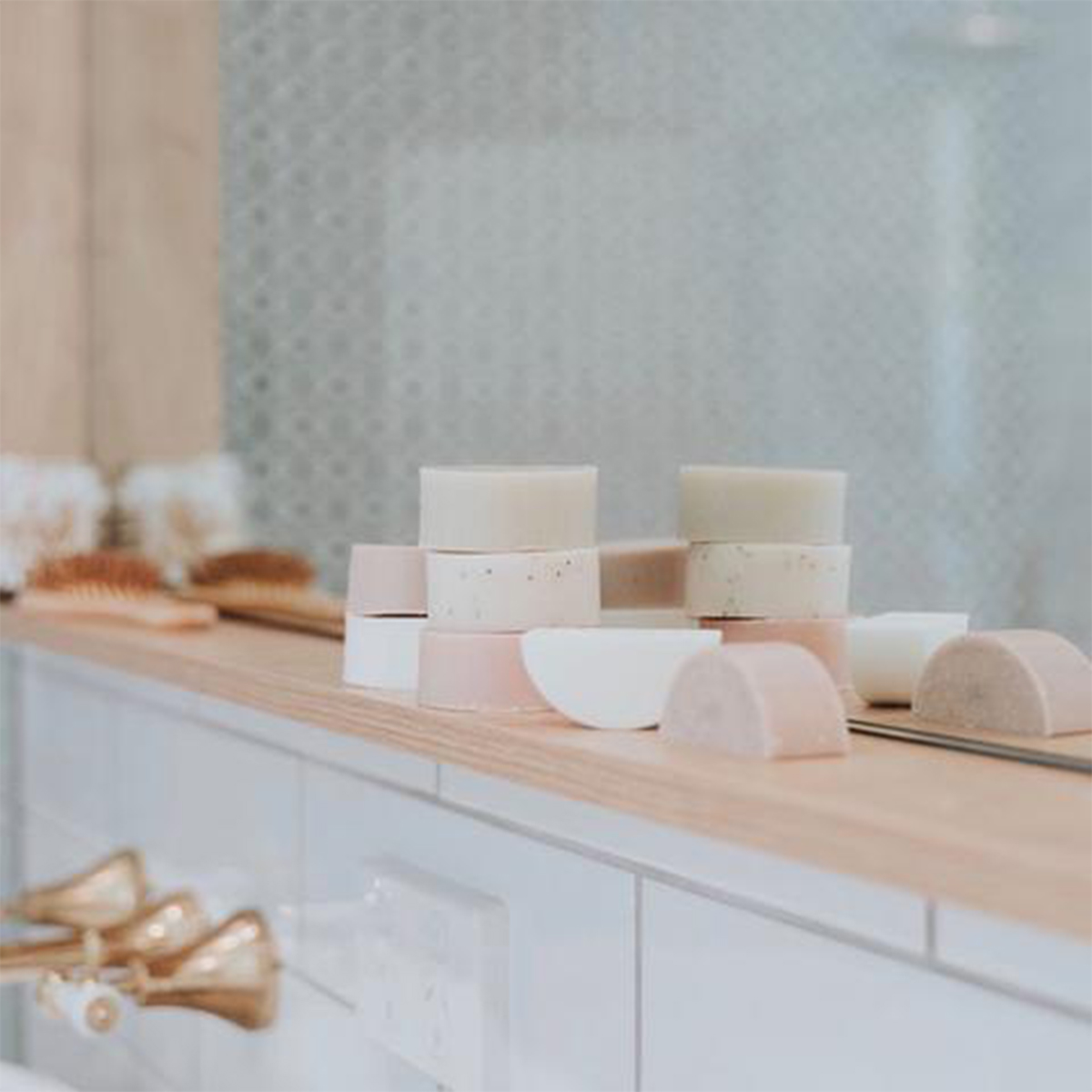 several soap bars lined and stacked on a bathroom mirror sill