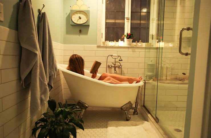 Woman in a bathtub in a homely bathroom, reading a book