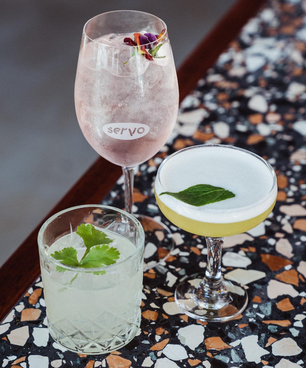 three cocktails on a terrazzo bar at Servo