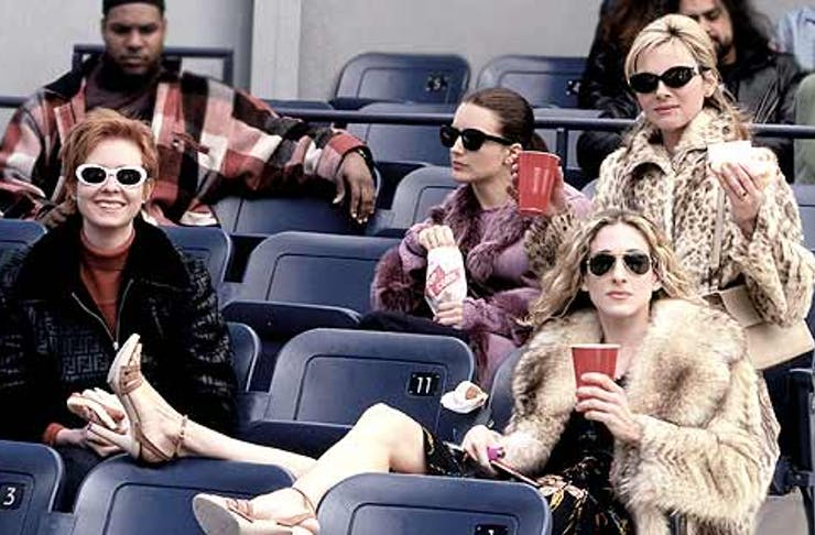 four women sitting on seats with big jackets and glasses