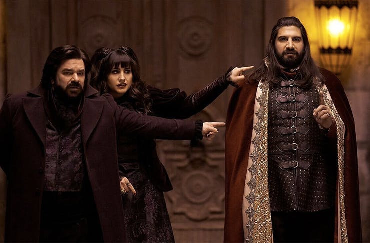Three main characters from What we do in the shadows stand in an old parlour wearing capes and other old accoutrements.