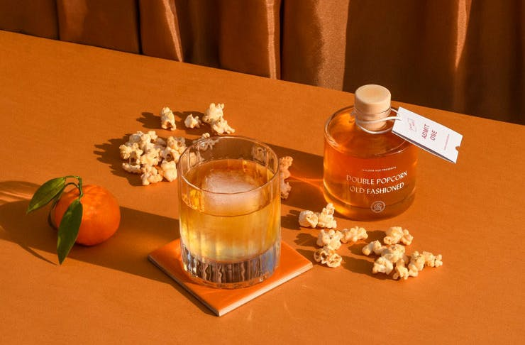 A bottled cocktail displayed with some popcorn.
